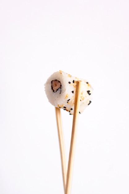 Mangiare sushi con le bacchette. rotolo di sushi cibo giapponese nel ristorante isolato su sfondo bianco. Foto Premium