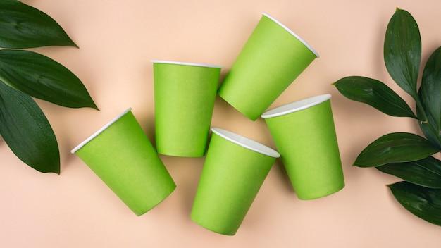 Stoviglie monouso ecologiche tazze e foglie verdi Foto Premium