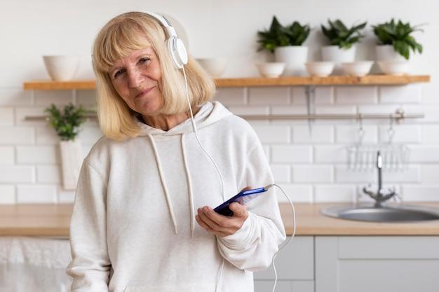 Donna anziana che gode della musica in cuffia a casa Foto Premium