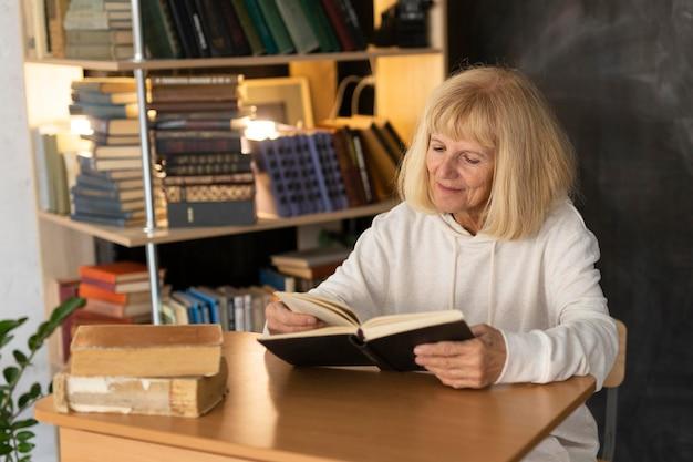 Donna anziana che legge un libro a casa Foto Premium