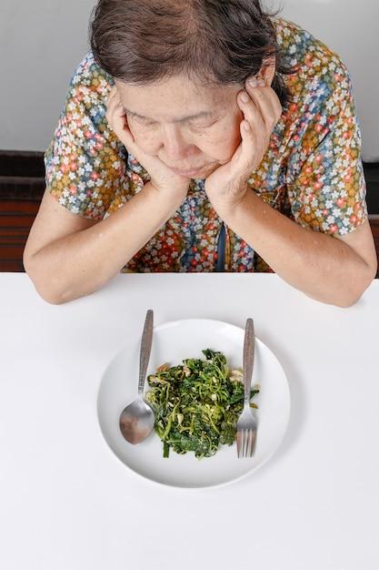 Donna asiatica anziana annoiata con il cibo Foto Premium