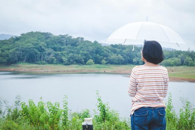 Una donna asiatica anziana tiene un ombrello bianco per evitare la pioggia. stare in piedi e guardare la vista naturale delle montagne durante la stagione delle piogge Foto Premium