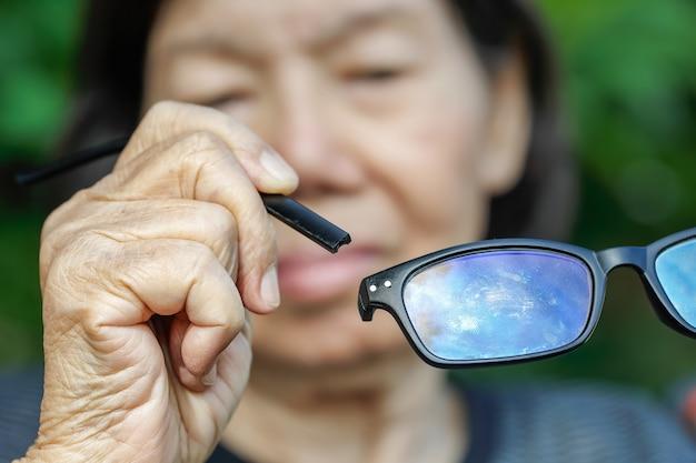Anziana donna asiatica riparazione vetri rotti Foto Premium