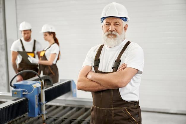 Ingegnere anziano che posa sulla fabbrica di lavorazione dei metalli. Foto Premium