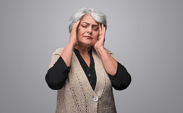 Signora anziana che soffre di emicrania pesante Foto Premium
