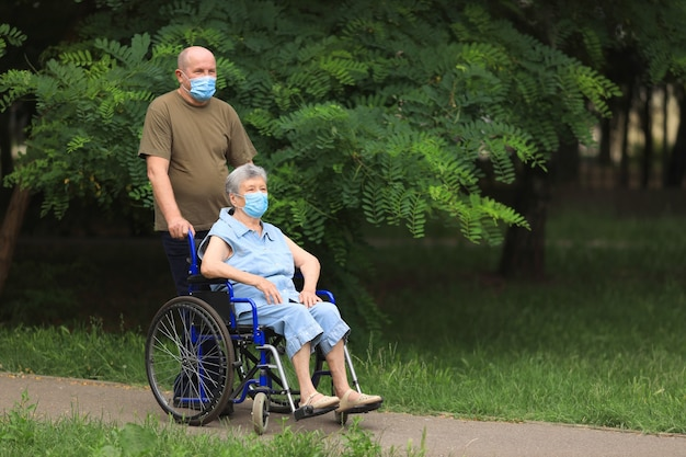 Uomo anziano che cammina con donna anziana disabile che si siede in sedia a rotelle all'aperto che indossa maschere mediche Foto Premium