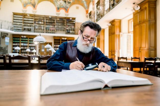 Uomo anziano con barba bianca e occhiali lavorando in un'antica biblioteca con libri, seduto al tavolo d'epoca. istruzione, concetto di biblioteca Foto Premium