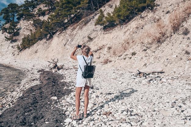 Anziani senior viaggio zaino in spalla donna matura turista a piedi scattare foto sulla costa Foto Premium