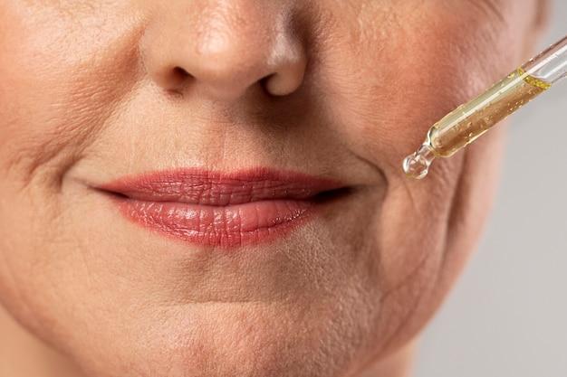 Donna anziana che utilizza il siero per le rughe della bocca Foto Premium