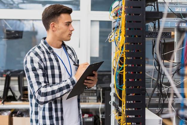Ingegnere elettrico che osserva sullo switch di rete Foto Premium