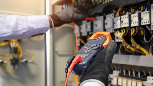 Ingegnere elettrico che utilizza apparecchiature di misurazione per controllare la tensione della corrente elettrica all'interruttore. Foto Premium
