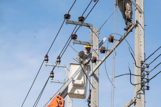 Elettricista sugli ascensori che lavorano per riparare le linee elettriche Foto Premium