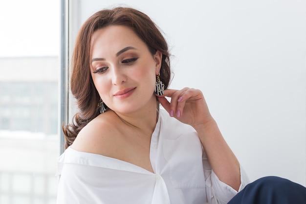 Elegante donna con orecchini gioielli in argento e catena Foto Premium