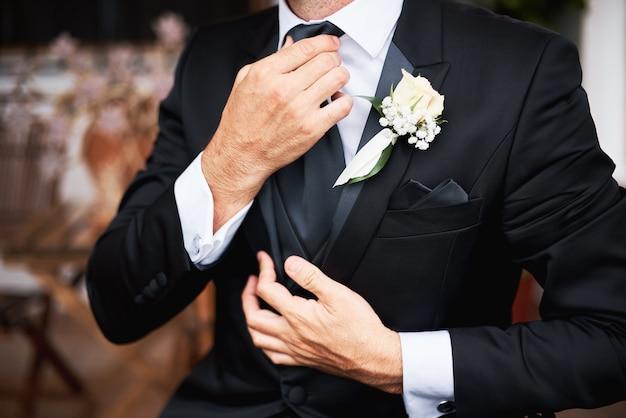 Elegnat sposo in abito elegante nero che indossa una cravatta la mattina prima del matrimonio. Foto Premium