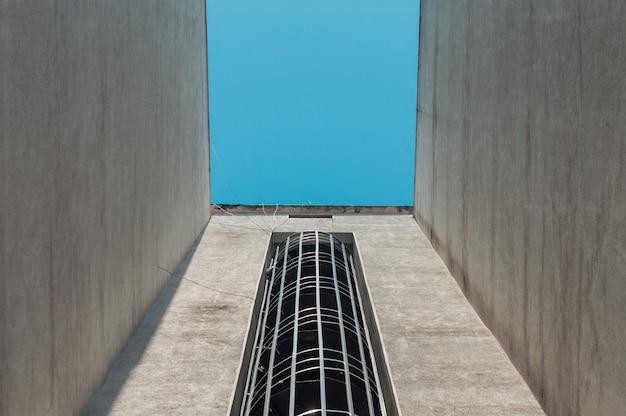 Scale dell'uscita di sicurezza di emergenza su una costruzione esteriore con cielo blu qui sopra Foto Premium