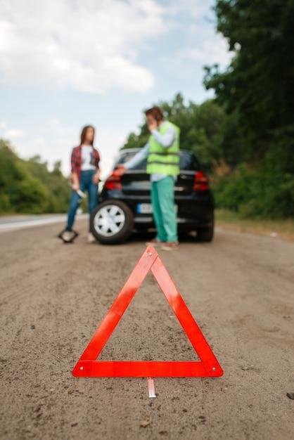 Segnale di arresto di emergenza, guasto alla macchina, coppia che chiama per carro attrezzi. Foto Premium