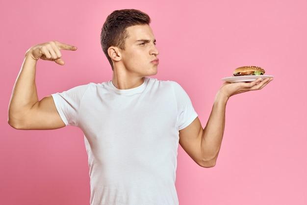 Ragazzo emotivo con hamburger su un piatto e t-shirt bianca sfondo rosa vista ritagliata di calorie fast food. foto di alta qualità Foto Premium