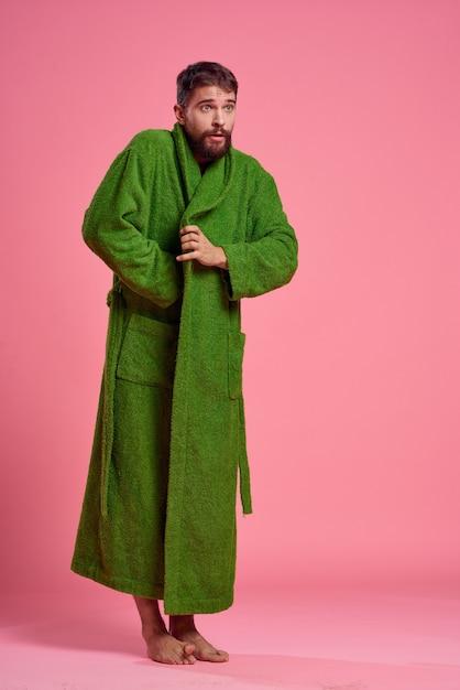 Un uomo emotivo in una veste verde in piena crescita su una rosa Foto Premium