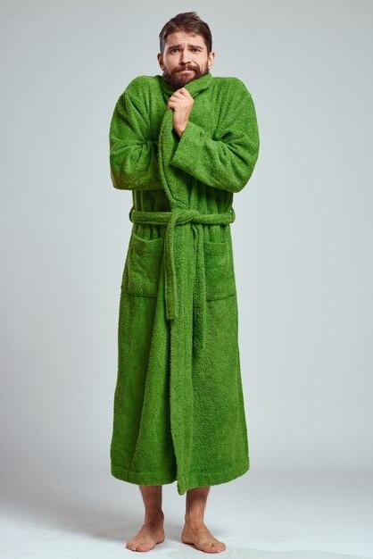 Uomo emotivo in una veste verde su grigio Foto Premium