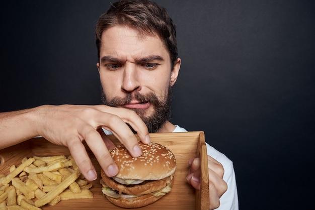 Uomo emotivo con patatine fritte in legno pallet fast food hamburger mangiare cibo lifestyle sfondo scuro. foto di alta qualità Foto Premium