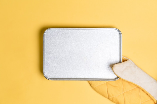 Svuotare il piatto da forno posto all'interno dei guanti da forno gialli su sfondo di colore giallo. Foto Premium