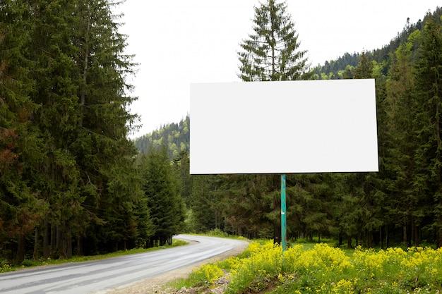 Tabellone per le affissioni vuoto o grande bordo dal lato della strada con la foresta e le colline verdi. pubblicità in bianco, mock up Foto Premium