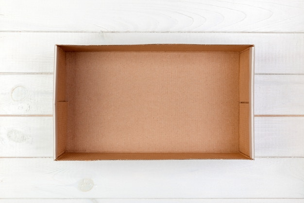 Scatola di cartone vuota su una vista superiore del fondo di legno bianco Foto Premium