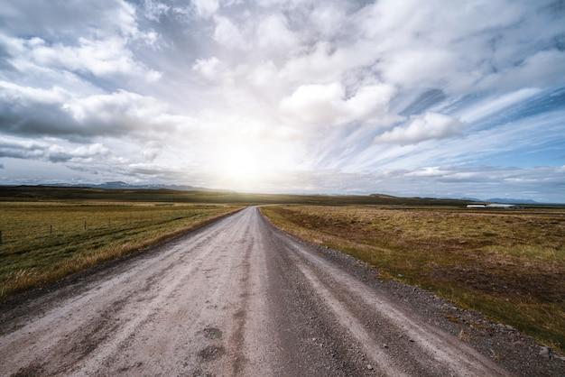 Strada non asfaltata vuota attraverso il paesaggio della campagna. Foto Premium