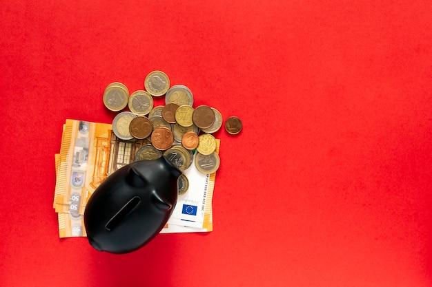 Svuotare il salvadanaio con la quantità di risparmio accanto ad esso su un tavolo rosso. concetto di risparmio di denaro Foto Premium