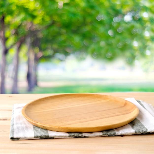 Svuoti il vassoio di legno rotondo e la biancheria da tavola sulla tavola sopra il fondo dell'albero della sfuocatura, per il montaggio dell'esposizione del prodotto e dell'alimento, modello Foto Premium