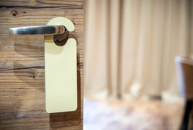 Un segno vuoto sulla maniglia della porta dell'hotel per il testo Foto Premium
