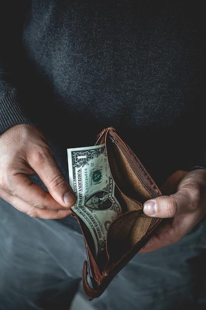 Portafoglio vuoto nelle mani di un giovane Foto Premium