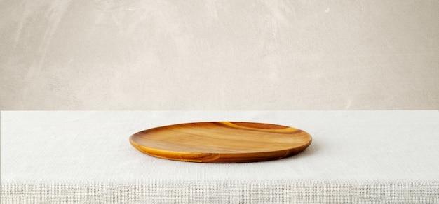 Svuoti il vassoio di legno sulla tovaglia del sacco isolata su fondo bianco. Foto Premium
