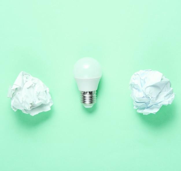 Lampadina led a risparmio energetico e palline di carta stropicciata su sfondo verde. concetto di business minimalista, idea. vista dall'alto Foto Premium
