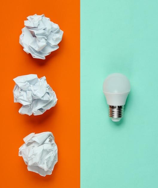 Lampadina led a risparmio energetico e palline di carta stropicciata su sfondo blu arancione. concetto di business minimalista, idea. vista dall'alto Foto Premium