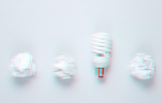 Lampadina a risparmio energetico e palline di carta stropicciata su sfondo grigio. effetto glitch. vista dall'alto Foto Premium