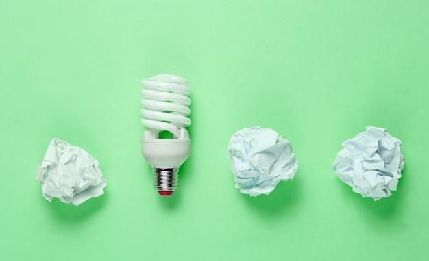Lampadina a risparmio energetico e palline di carta stropicciata su sfondo verde. concetto di business minimalista, idea. vista dall'alto Foto Premium