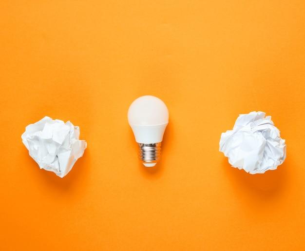 Lampadina a risparmio energetico e palline di carta stropicciata su sfondo arancione. concetto di business minimalista, idea. vista dall'alto Foto Premium