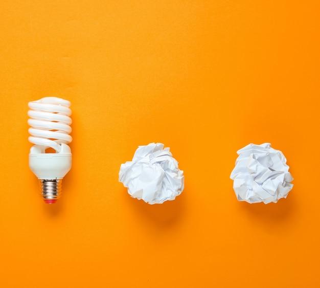 Lampadina a risparmio energetico e palline di carta stropicciata su sfondo giallo. concetto di business minimalista, idea. vista dall'alto Foto Premium