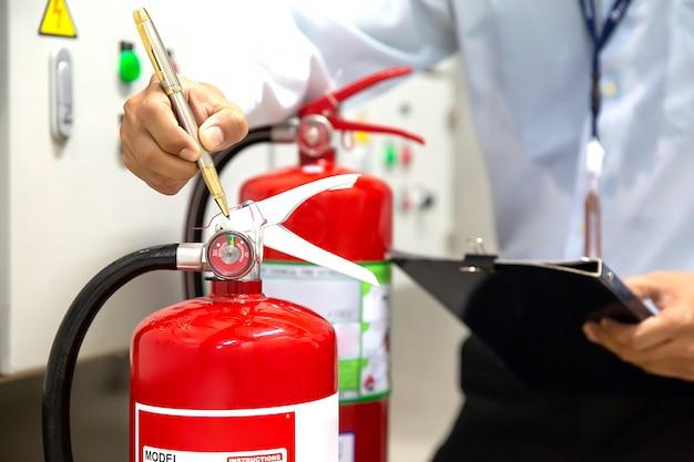 L'ingegnere sta controllando e ispezionando un estintore nella sala controllo incendi per sicurezza e prevenzione. Foto Premium