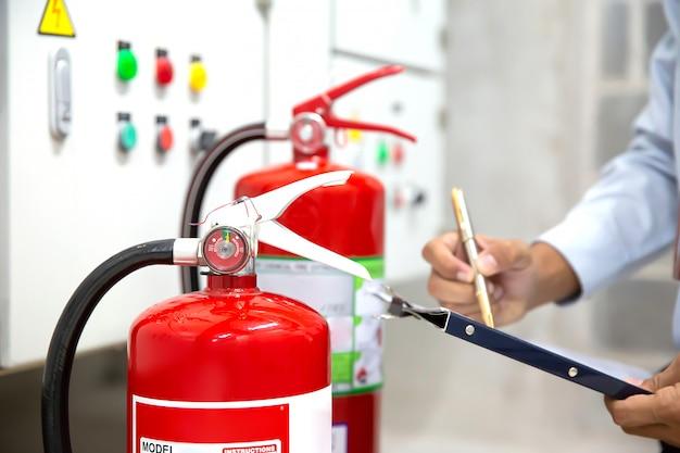 L'ingegnere sta controllando e ispezionando un estintore rosso nella sala di controllo antincendio per sicurezza. Foto Premium