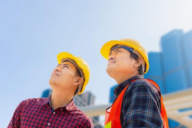 Uomo e lavoratore dell'ingegnere con il percorso di ritaglio che controlla e che progetta progetto al cantiere, uomo che esamina il cielo sopra fondo vago Foto Premium