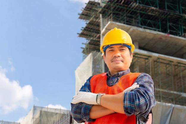 Uomo / lavoratore dell'ingegnere con il progetto di controllo e di pianificazione del percorso di ritaglio al cantiere, uomo sorridente sopra fondo vago Foto Premium