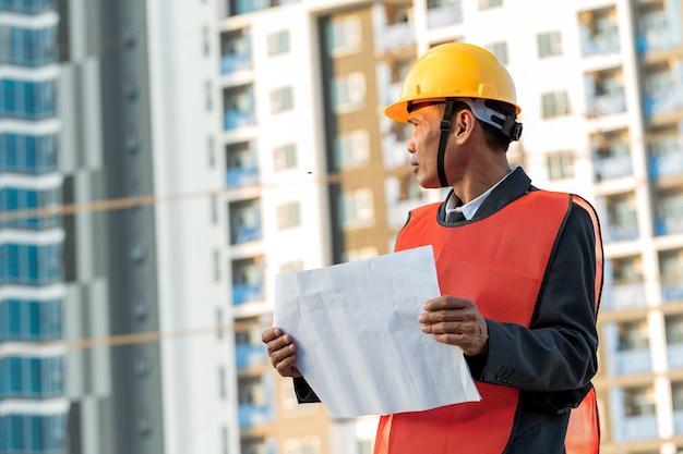 Ingegnere in piedi per ispezionare i piani di costruzione in cantiere Foto Premium