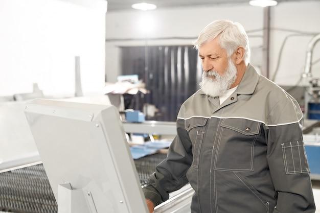 Ingegnere che lavora in fabbrica con macchina computerizzata. Foto Premium