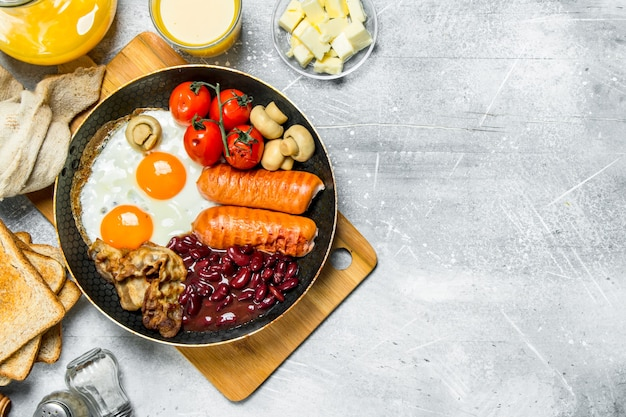 Colazione inglese. una varietà di snack con succo d'arancia. su una superficie rustica. Foto Premium