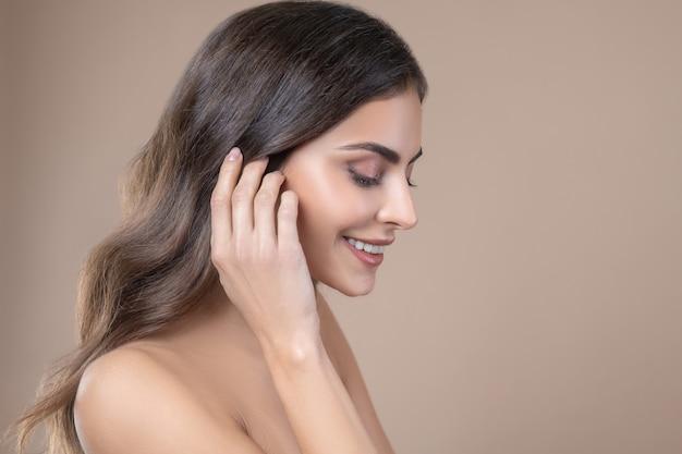 Aspetto enigmatico. bella felice bella giovane donna di profilo con le spalle nude palpebre cadenti e la mano vicino alla testa Foto Premium