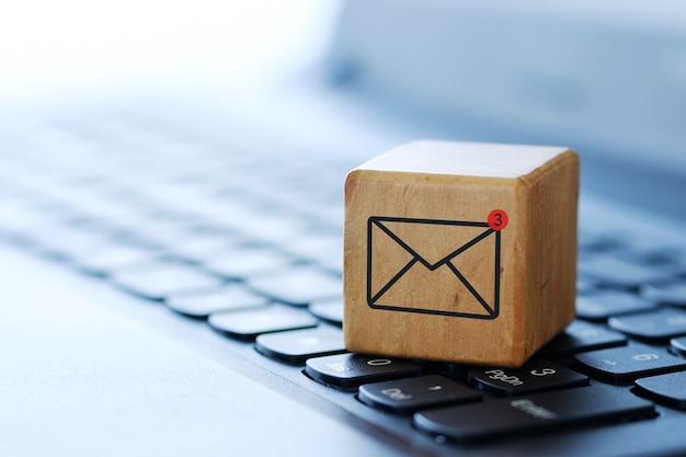 Un simbolo di busta su un cubo di legno sulla tastiera di un computer, con uno sfondo sfocato e una profondità di campo ridotta. Foto Premium