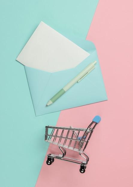 Busta con lettera e carrello della spesa su sfondo rosa pastello blu. mockup per san valentino, matrimonio o compleanno. vista dall'alto Foto Premium