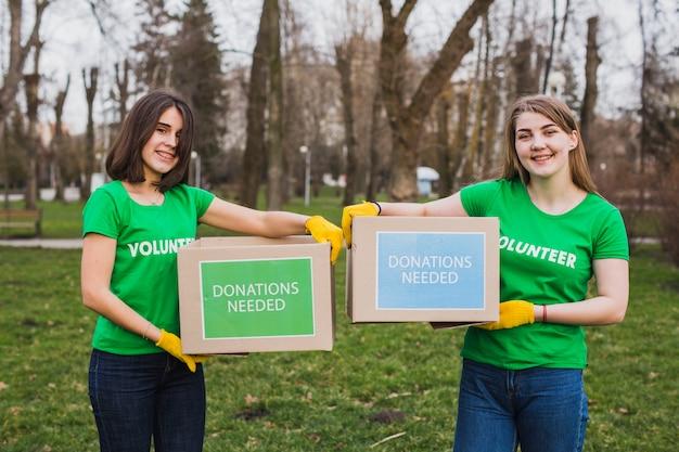 Ambiente e concetto di volontariato con persone che tengono le scatole per le donazioni Foto Premium
